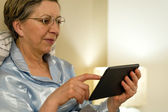 Senior woman using digital tablet in bed — Foto Stock