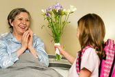 Girl giving bouquet of flowers to grandmother — Foto Stock