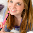 Smiling teenage girl daydreaming over her diary — Stock Photo