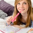Daydreaming teenager girl writing her journal - Stock Photo