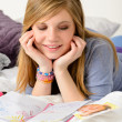 Friendly girl fantasizing over her diary — Stock Photo
