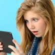 Surprised young girl holding digital tablet — Stock Photo