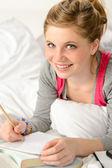 Smiling girl preparing for exams in bed — Stock Photo