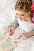 10 代の少女はベッドの中で勉強に集中して — ストック写真
