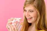 Elated girl opening gift — Stock Photo