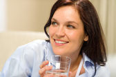 Smiling brunette woman with glass of water — Stock Photo