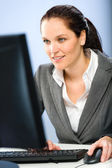 Smiling businesswoman working on her computer — Stock Photo
