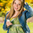 Stock Photo: Perky female teenager texting in park