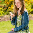 Young girl in park using her phone — Stock Photo