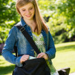 Stock Photo: Happy student girl with bag standing outside