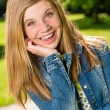 Portrait of smiling teenage girl outside - Stock Photo