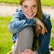 Cheerful teenage girl sitting in the park — Stock Photo