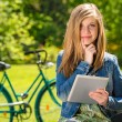 Pensive teenager in park with tablet — Stock Photo