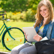 Young girl reading on tablet sunny day — Stock Photo