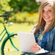 Adolescent girl using tablet computer in park — Stock Photo