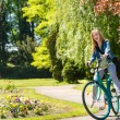 Laughing girl riding bicycle in the park — Stock Photo