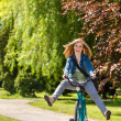 Carefree teenager riding bicycle across the park — Stock Photo