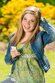 Perky female teenager texting in the park — Stock Photo