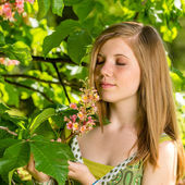 Young girl smelling blossom of the tree — Stock Photo