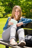 Young female student studying in the park — Stock Photo