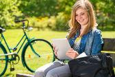 Giovane ragazza leggendo giorno soleggiato tavoletta — Foto Stock