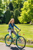 Girl enjoying summer break riding bicycle — Stock Photo