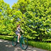 Happy woman riding fast her bike — Stockfoto