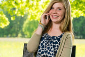 Smiling young girl using her mobile phone — Stock Photo