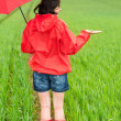 Stock Photo: Woman standing in raincoat and with umbrella