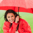 Wet young girl enjoying rainfall with umbrella — Stock Photo #26352673