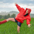 Playful teenage girl dancing in the rain — Stock Photo