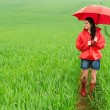 Stock Photo: Smiling young woman standing on rainy day