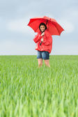 Elated teenage girl holding red umbrella — Stock Photo