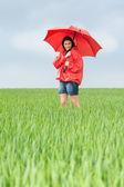 Elated teenage girl holding red umbrella — Stock Photo