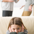 Stock Photo: Little girl is troubled because parents arguing