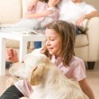 Playful girl petting family dog with parents — Stock Photo #26418079