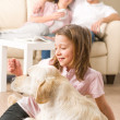 Playful girl petting family dog with parents - Stockfoto