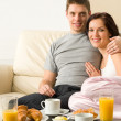 Cheerful couple sitting on couch before breakfast — Stock Photo #26418107