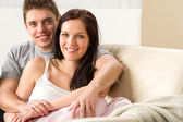 Carefree young couple embracing on couch — Stock Photo