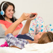 Teen girls relaxing on bed checking phone — Stock Photo
