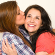 Girl gives kiss to best friend's face — Stockfoto #26753445
