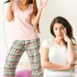 Young girl annoyed with her friend singing — Foto de Stock