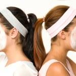 chicas sentadas espalda con espalda con máscara facial — Foto de Stock