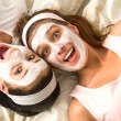 Crazy girls with facial mask lying bed — Stockfoto #26753545