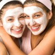 Blissful girls applying mask hugging each other — Stock Photo