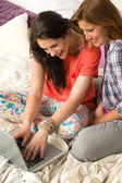Laughing girls chatting with friends online — Stock Photo