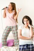 Young girl annoyed with her friend singing — Stock Photo