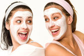 Cheerful girls having facial mask and laughing — Stock Photo