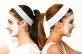 Girls sitting back-to-back wearing facial mask — Stock Photo