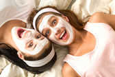 Crazy girls with facial mask lying bed — Stock Photo